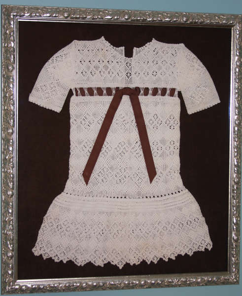 Shadowbox of an old crocheted baby dress